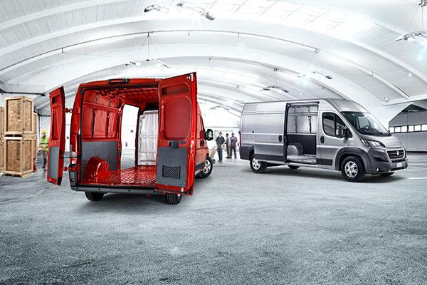 Zwei Fiat Ducato mit offenen Hecktüren und offener Seitentür in einem Lager