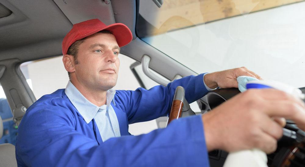 Mann putzt Transporter-Cockpit.