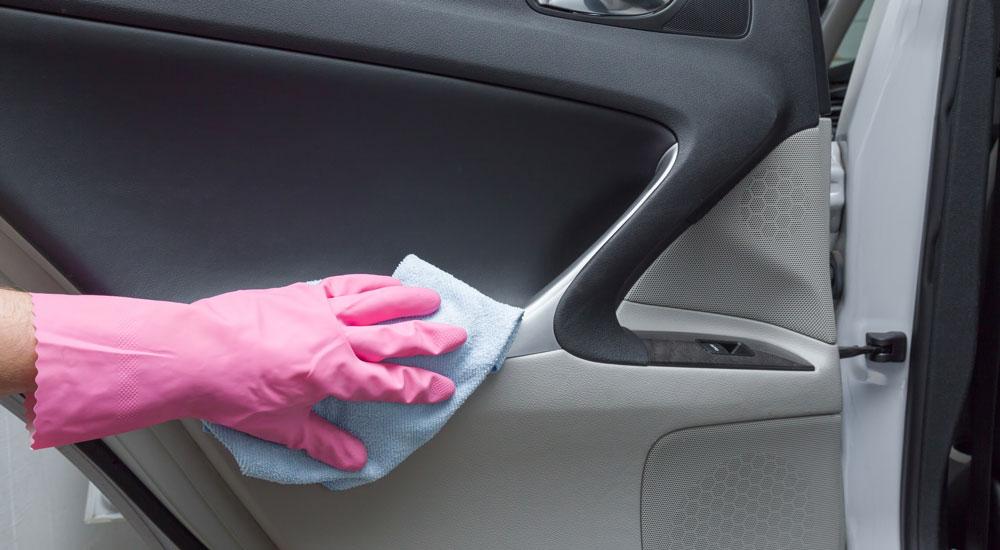 Nahaufnahme einer Hand bei der Reinigung eines Transporter-Cockpits.